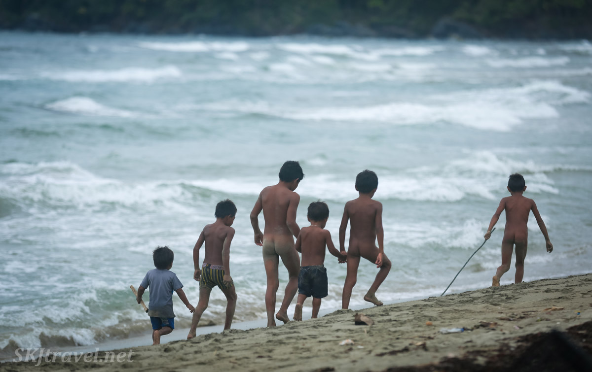 Children walking along the beach, holding hands, Armila, Guna Yala, Panama.