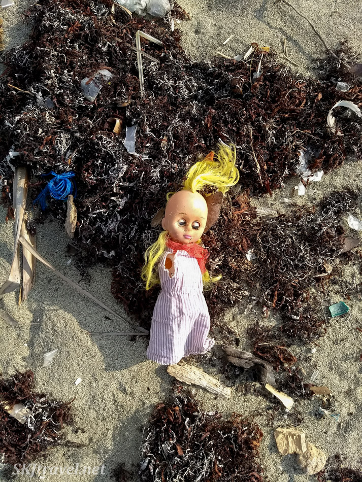 Plastic doll among the heaps of trash along the beaches of Armila, Guna yala, Panama.