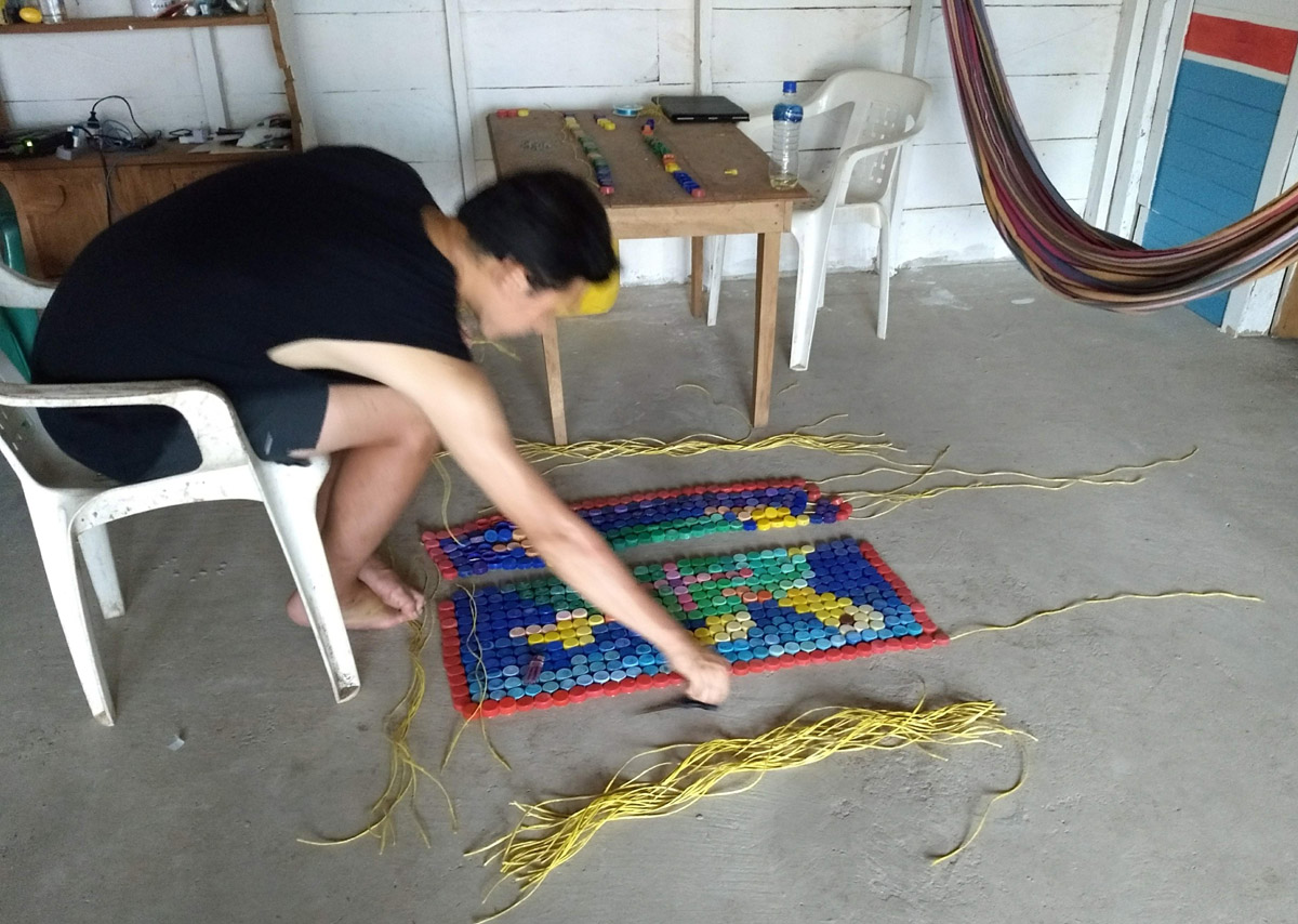 Chong stitching together plastic bottle caps in shape of a turtle. La Wayaka Artist Residency, Armila, Guna Yala, Panama.