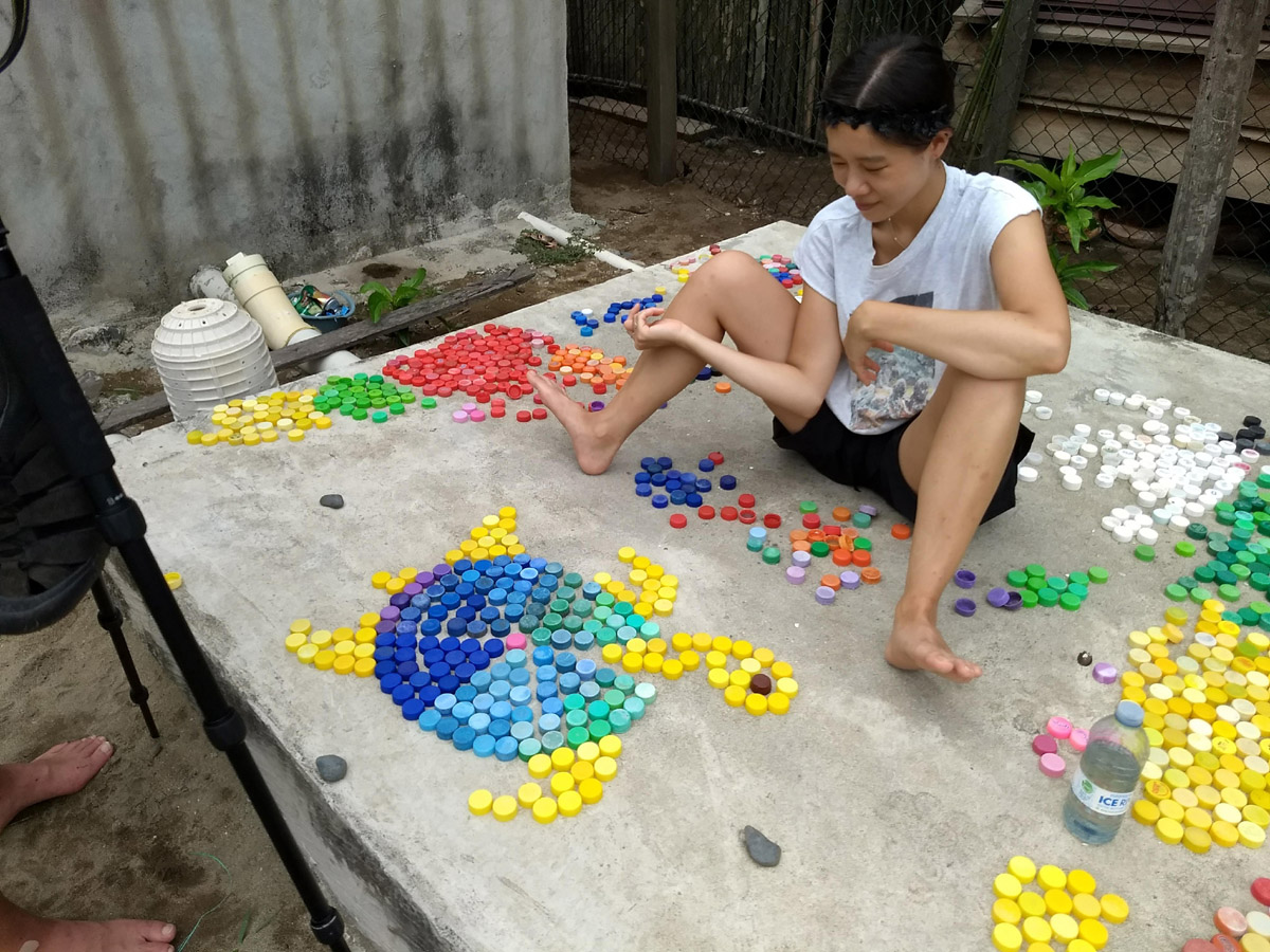 Yoon placing plastic bottle caps in shape of a turtle. La Wayaka Artist Residency, Armila, Guna Yala, Panama.