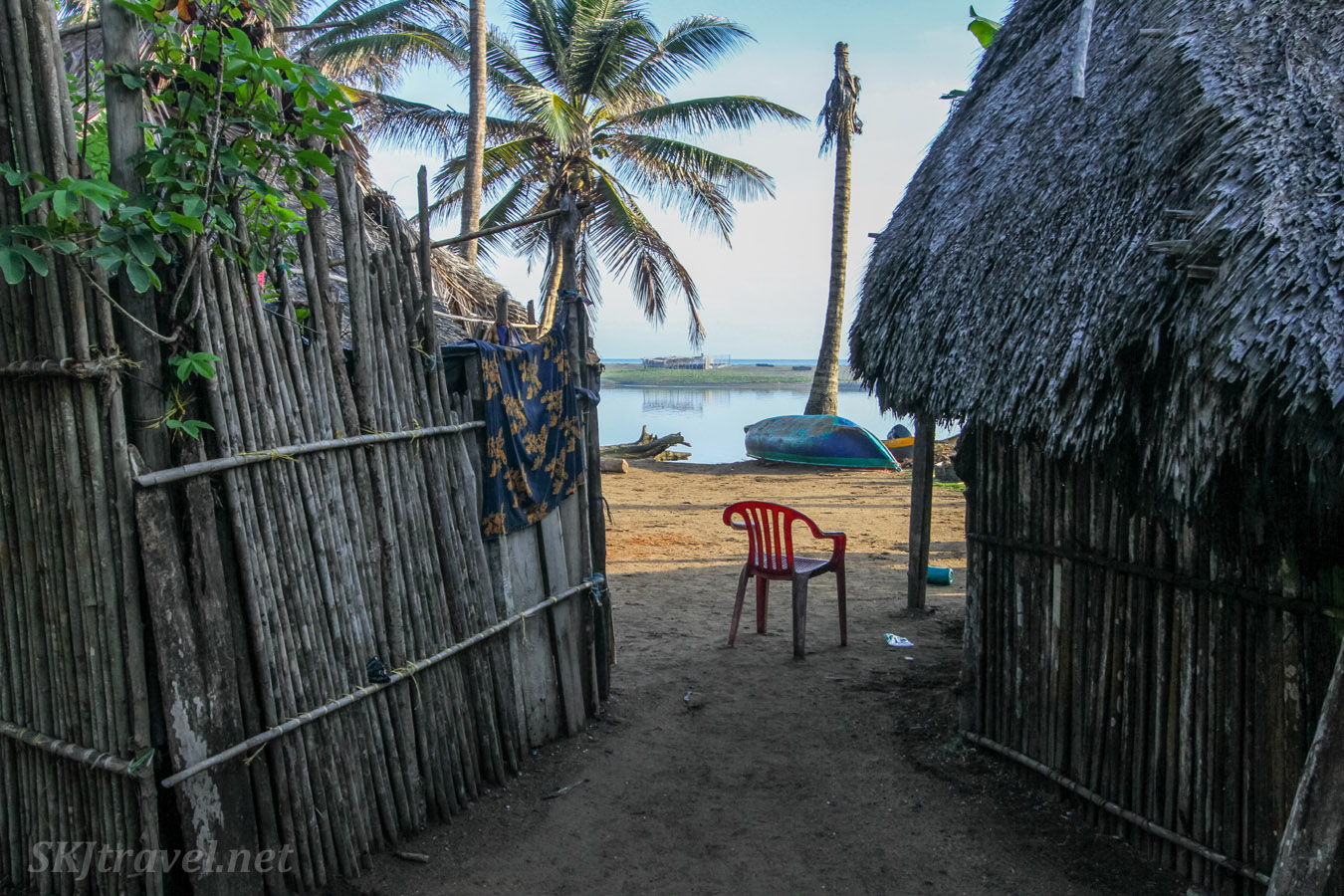 Red plastic chair between bamboo huts on the shore of Armila River. Armila, Guna Yala, Panama. La Wayaka Current.