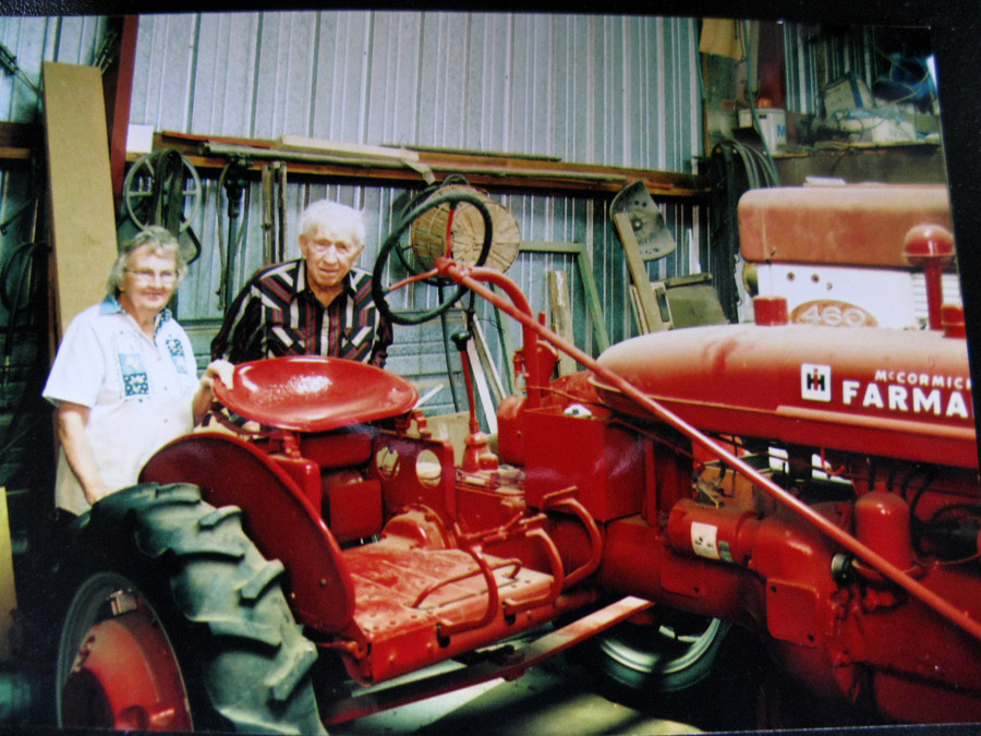 Grandma and Grandpa standing next to an old tractor they had refinished. Inside their shop, Cozad, Nebraska.