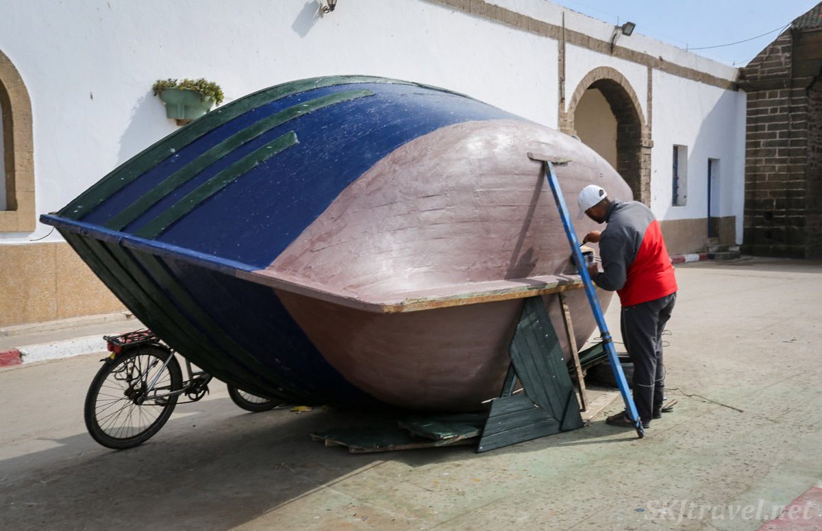 Man repairing and painting a boat, Essaouira, Morroco.