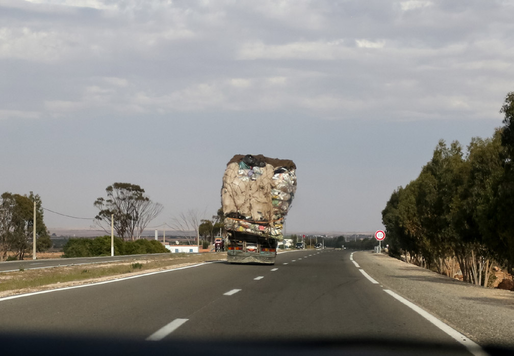 Overloaded lopsided truck on the road between Marrakech and Essaouira, Morocco.