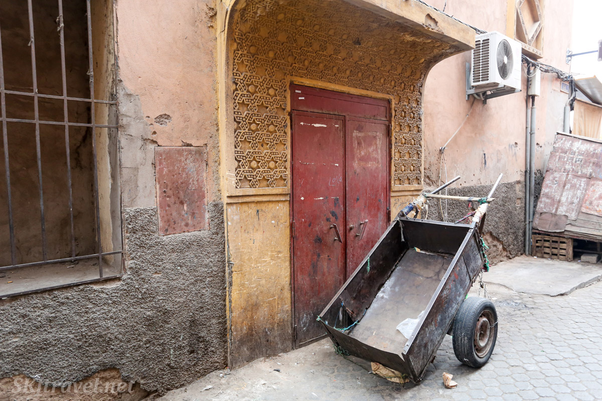 Wheelbarrow in front of a door in residential area of Marrakech medina, Morocco.