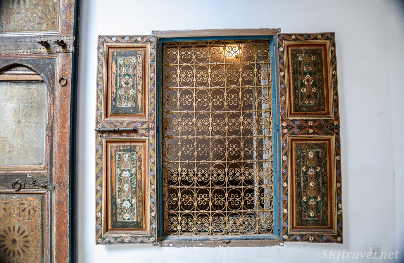 Window with painted wooden shutters and fancy grate. Bahia Palace, Marrakech, Morocco. UNESCO World Heritage.