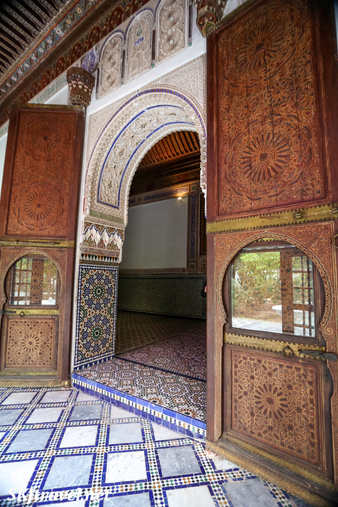 Very tall wooden doors with Moroccan carved stucco doorway arch, tile floor. Bahia Palace, Marrakech, Morocco. UNESCO World Heritage.