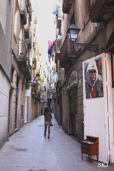 Very narrow alleyway line with tall buildings and colorful banners in Barcelona. Photo by Shara Johnson