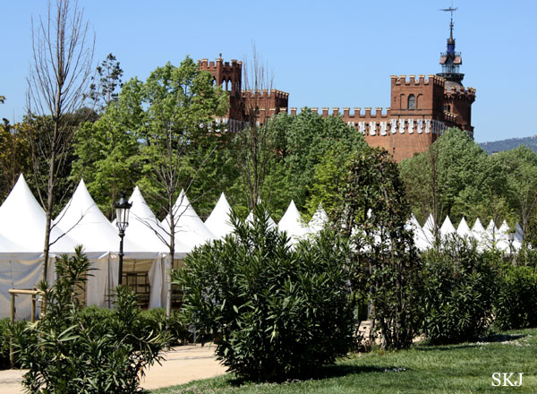 Small white tents with pointed roofs are lined up in a park in Barcelona. photo by Shara Johnson