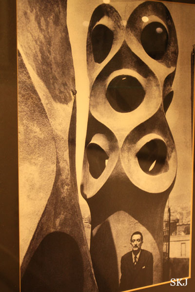 Sepia photograph of Dali standing next to a Gaudi rooftop sculture in Barcelona. Photo by Shara Johnson