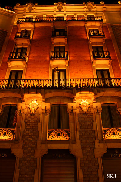 Tall red brick building with small balconies lit with yellow lights at night in Barcelona. Photo by Shara Johnson