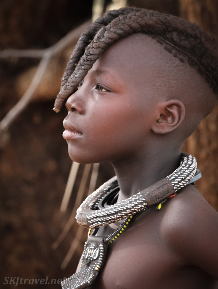 Himba girl with traditional two braids down the front of her face. Kunene region, Kaokoland, Namibia.