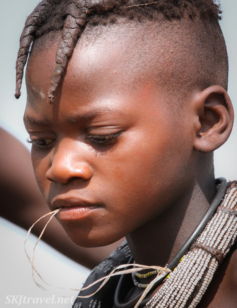 Himba girl chewing on a string. Kunene region of Kaokoland, Namibia.
