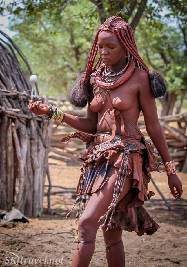 Princess Kaviruru carrying a spoon across her kraal. Himba village, northern Namibia.