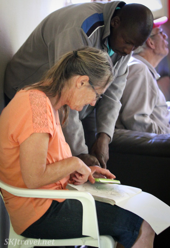 Alzheimer's patient at the ADN care farm near Swapkopmund, Namibia, working in a coloring book.