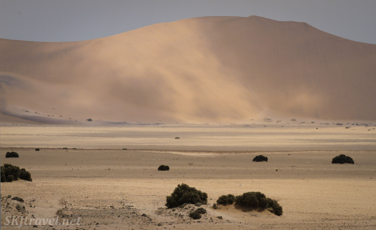 Sand blowing down the dunes of the Namib Desert near Swapkopmund, Namibia.
