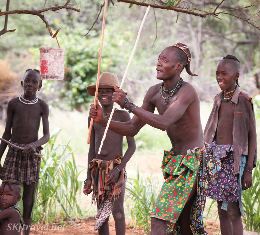 Young Himba man wielding traditional stick-fighting sticks. Near Epupa Falls, Namibia.