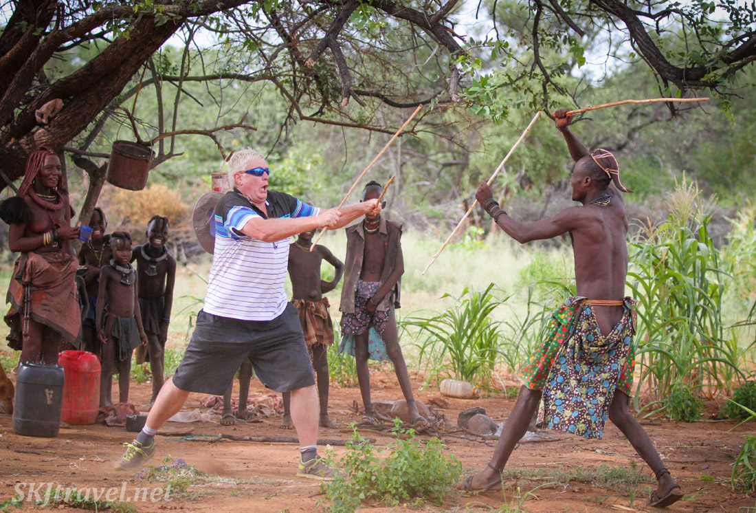 Go Berrie! Traditional stick-fighting in Kaokoland, Namibia: white man versus Himba man.