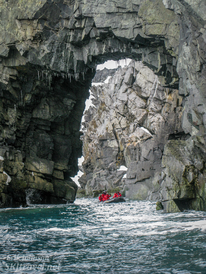Zodiac heading through a large arch at Spert Island, Antarctica.