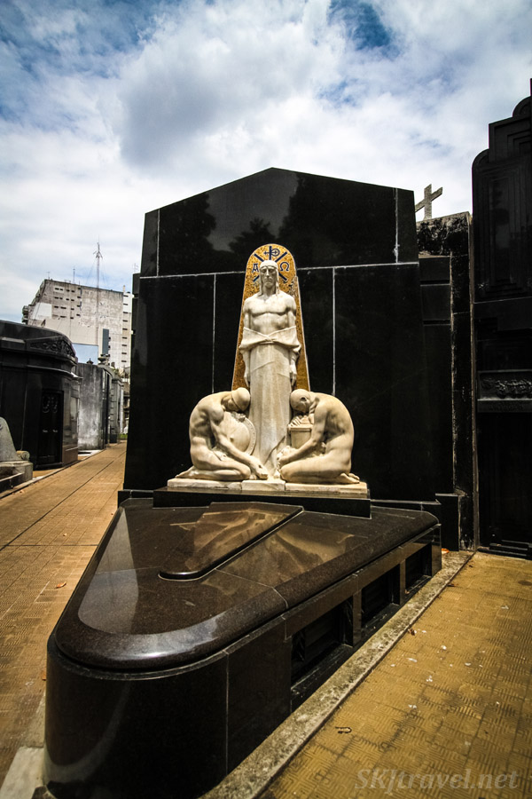Stone statue on a marble tomb in Recoleta Cemetery, Buenos Aires, Argentina.