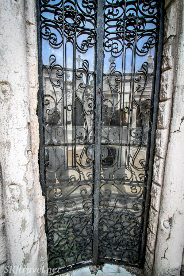 Decorative door to a mausoleum with reflections in Recoleta Cemetery, Buenos Aires, Argentina.
