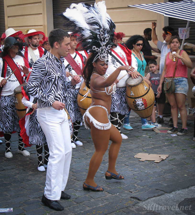 Festive dressed woman, Carnaval style, leading a comparsa in the San Telmo Candombe parade, Buenos Aires, Argentina.