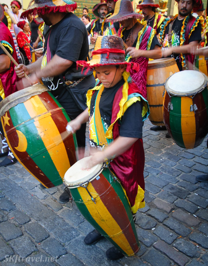 Young boy playing a tamborile mano y palo, with a stick and hand, in the San Telmo Candombe parade, Buenos Aires, Argentina.