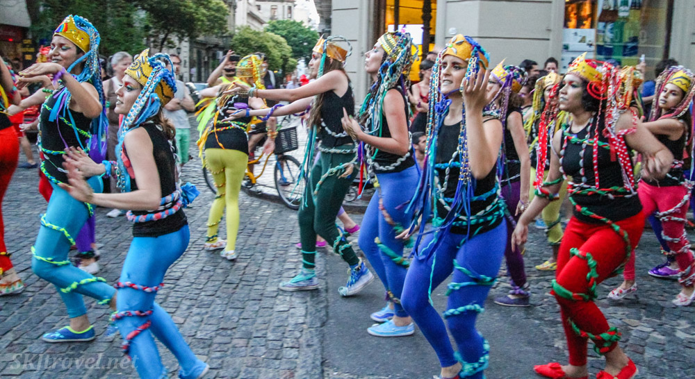 Women dancing down the cobblestone streets in the San Telmo Candombe parade, Buenos Aires, Argentina.