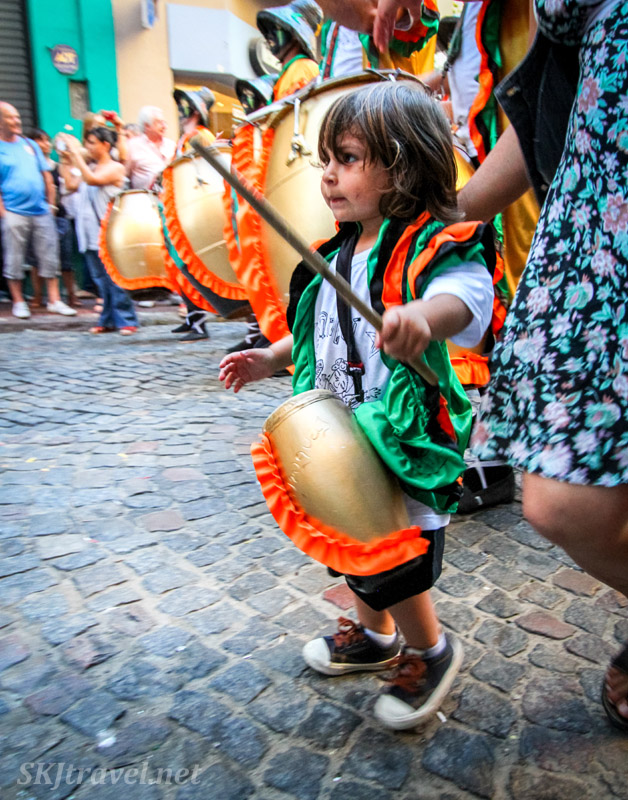 Small child playing a tiny tamborile in the San Telmo Candombe parade, Buenos Aires, Argentina.