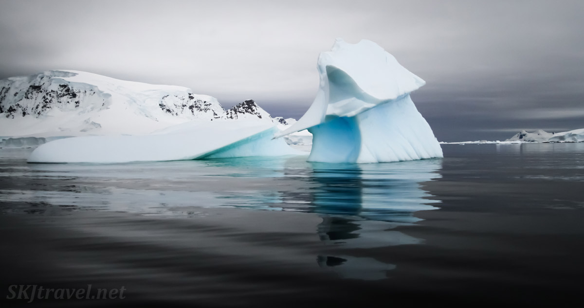 Wilhelmina Bay, iceberg reflected on gray, still water. Antarctica.