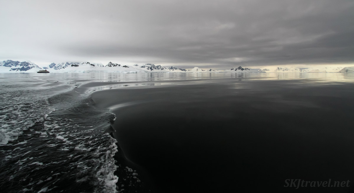 Wilhelmina Bay, dark gray waters and golden mountains. Antarctica.