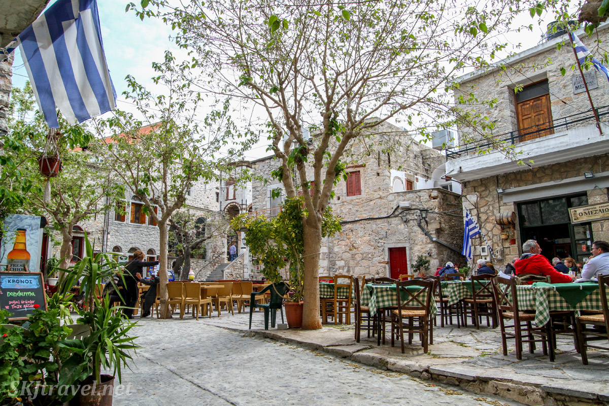 Central courtyard with restaurants and cafes, full of people in the medieval labyrinth of streets in the mastic Mesta village, Chios Island, Greece.