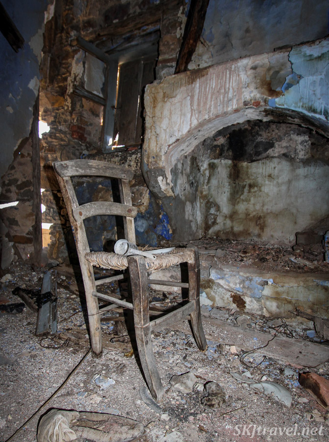 Old wicker seat chair inside an abandoned home in Volissos, Chios Island, Greece. Sitting next to a fireplace, stone and plaster rubble on the floor.