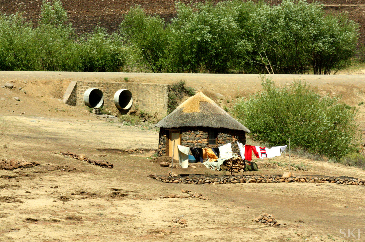 Typical traditional round, thatched-roof rondeval home in Lesotho. Laundry drying on the line.