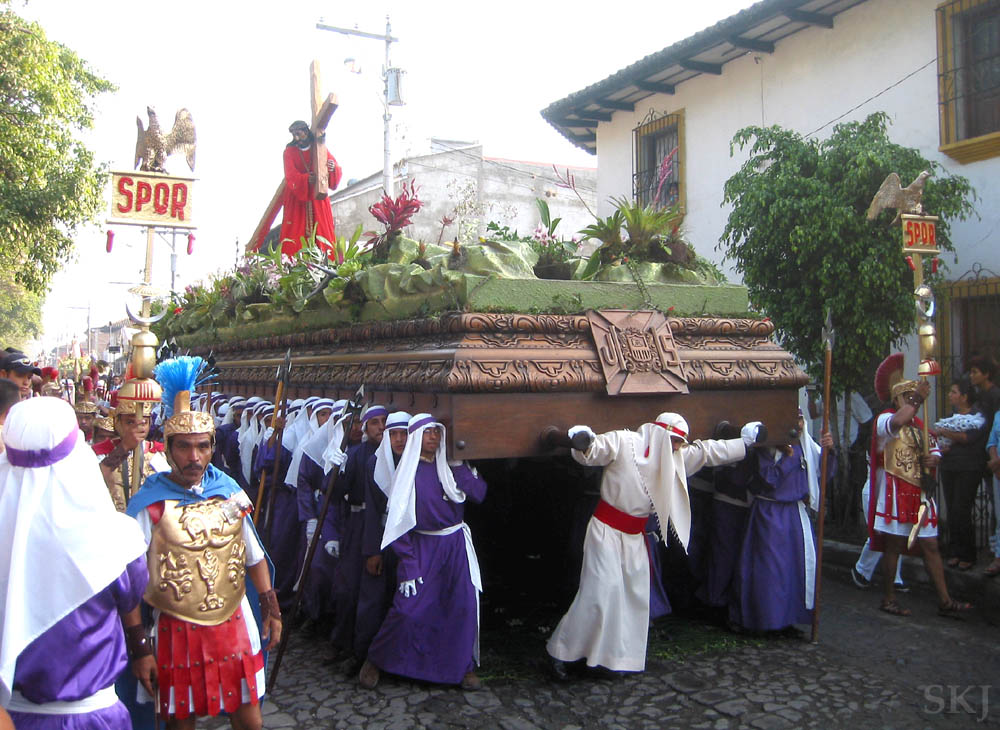 Men dressed in purple carry floats carved of solid wood, holding Jesus with the crucifix, through the streets of Antigua, Guatemala, for Semana Santa celebration. Good Friday morning.