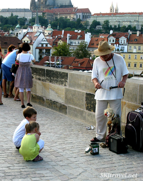 Kids raptly watching a puppeteer on the Charles Bridge. Prague.