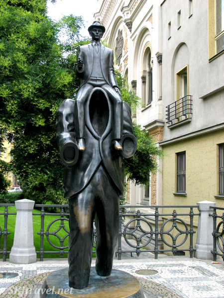Metal statue of a man sitting on the shoulders of an empty man's suit. Ode to Kafka in Prague