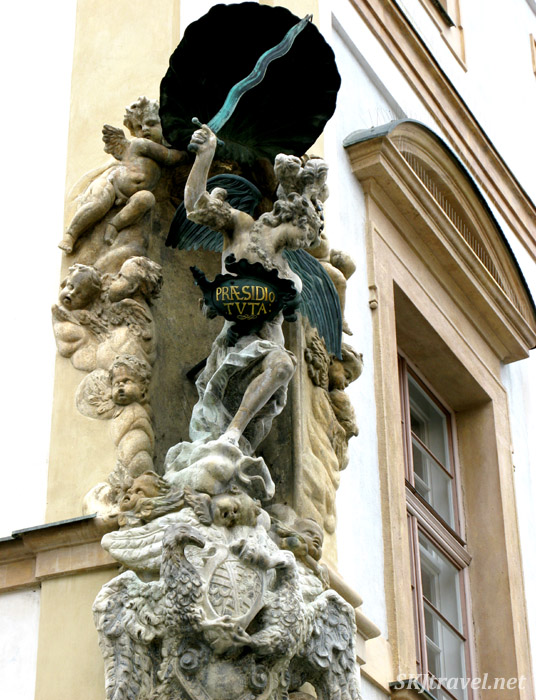 Statues embedded in the corner of a building, winged lady with sword stepping on cherub heads. Prague.