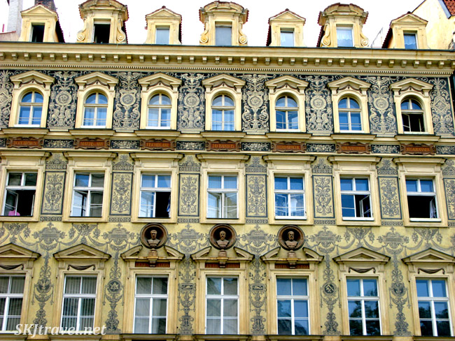 Ornate exterior of building in Prague complete with busts of men.