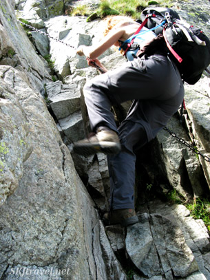 Shara pulling herself up with the chains bolted into vertical cliff face. High Tatras, Slovakia.