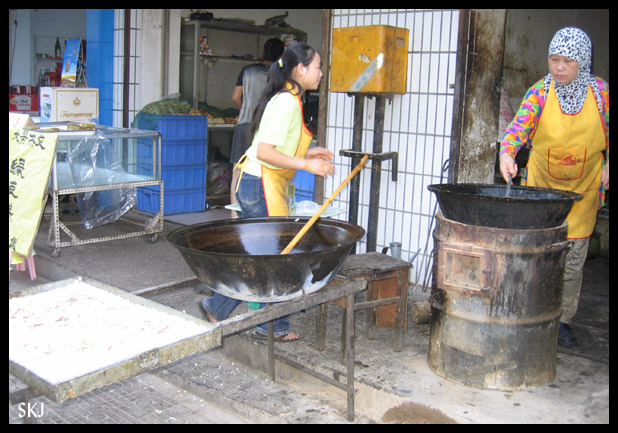 Huge pots of noodles being stirred on a sidewalk in the Muslim Quarter in Xian, China.