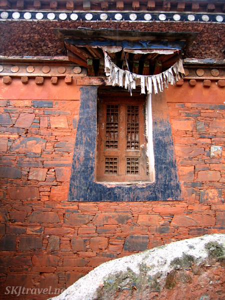 Window in a red-painted stone building at the Labrang Monastery. Xiahe, China.