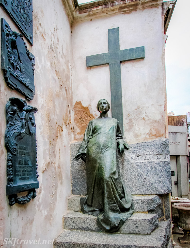Mausoleum in the Recoleta Cemetery, Buenos Aires, with bronze cross on the wall and bronze statue of a lady with her bronze skirt flowing down the stone stairs.