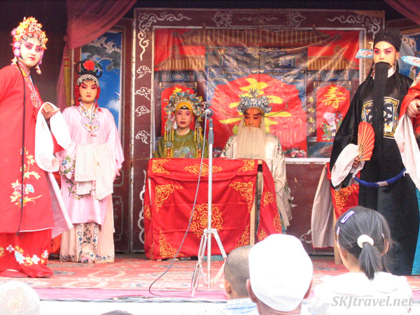 Performers on stage, performing Peking opera at the rain festival in Wang Jia Bian, Shaanxi Province, China.