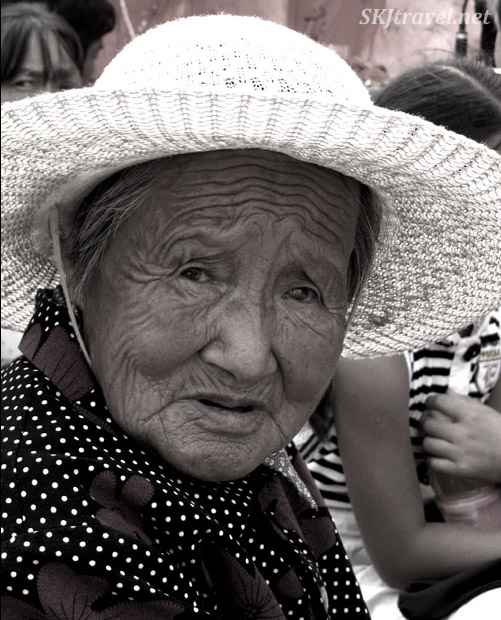 A sepia image of an elderly Chinese woman with a white hat, northern Shaanxi Province. Photo by Shara Johnson