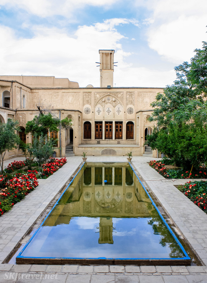 Courtyard with long reflecting pool of  Borujerdi House, wind catcher tower rising up behind it. Blue sky reflecting in pool. Kashan, Iran.