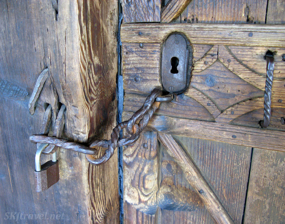 Metal keyhole, padlock and chain on wooden door to a small church on the roadside, Slovakia.