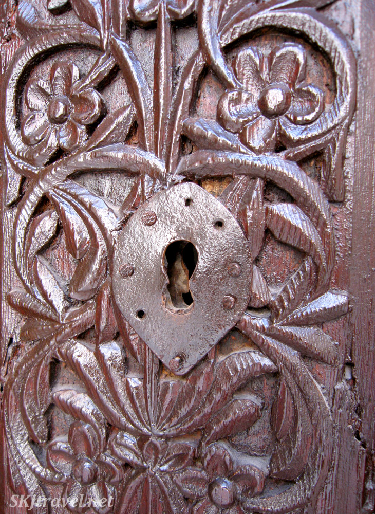 Metal keyhole in brown painted carved wooden door, Wroclaw, Poland.