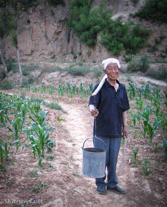 Papa Dang carrying water home in buckets on a shoulder pole from the spring in Dang Jia Shan valley.