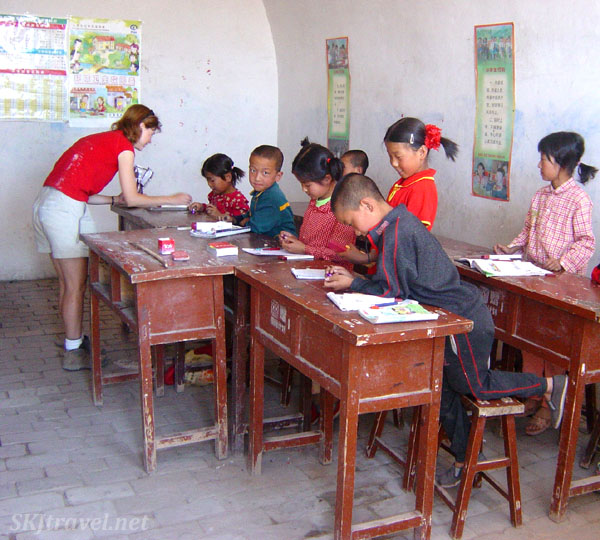 School children in their classroom in rural China receiving gifts of chocolate and stickers. Photo by Shara Johnson.